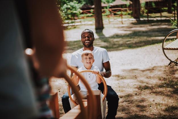 Happy family people joue à la bascule sur un terrain de jeu Photo Premium