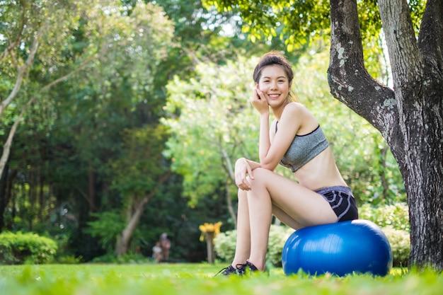 Happy fit jeune femme exerçant avec ballon de fitness dans un parc Photo Premium