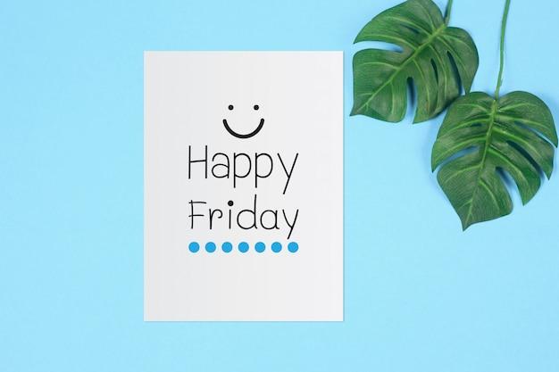Happy friday sur une feuille blanche avec une feuille de palmier tropical vert sur fond de couleur bleue Photo Premium