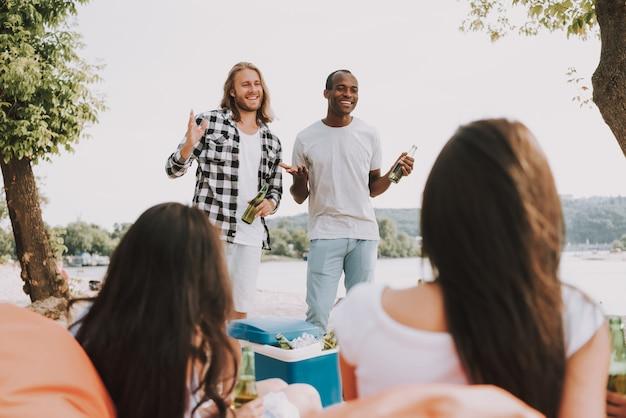 Happy friends a obtenu de la bière à la fête sur la plage Photo Premium