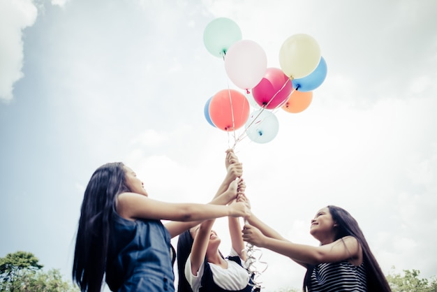 Happy girl girl friends tenant des ballons multicolores Photo gratuit