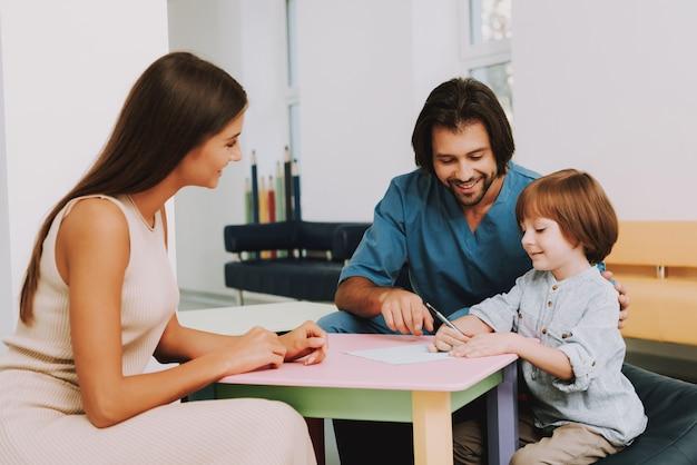 Happy Kid Dessine à La Clinique Pédiatrique De Doctor Office. Photo Premium