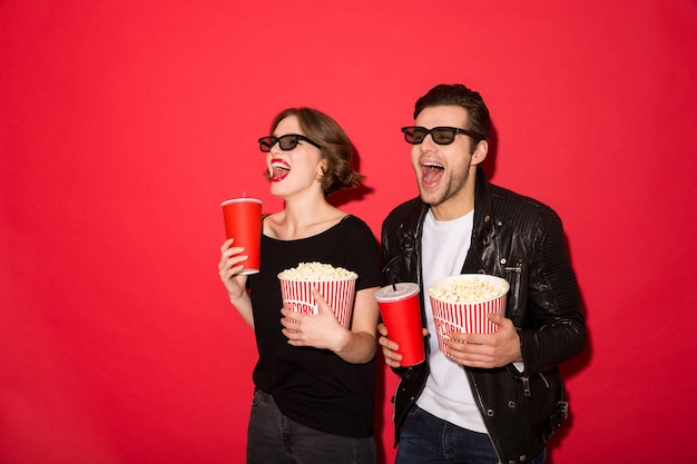 Happy Punk Couple In Eyeglasses Holding Soda And Popcorn Photo gratuit