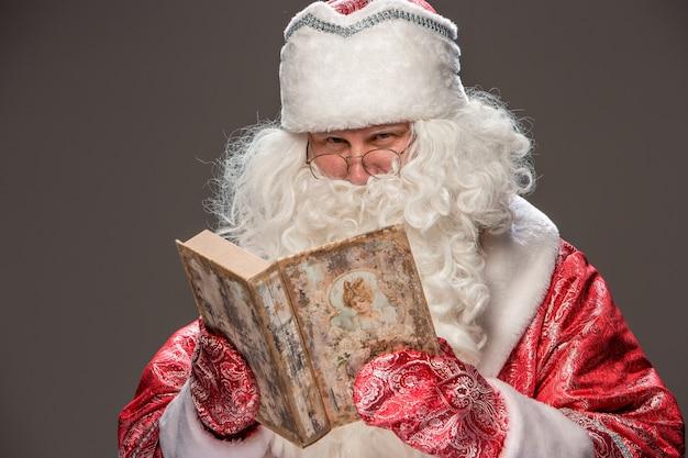 Happy Santa Claus à Lunettes, Lecture De Vieux Livre Sur Fond Sombre Photo gratuit