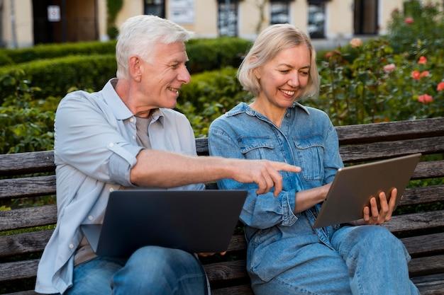 Happy Senior Couple Sur Banc à L'extérieur Avec Ordinateur Portable Et Tablette Photo gratuit