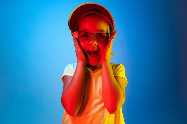 Happy Teen Girl Debout Et Souriant Isolé Sur Un Espace Néon Bleu à La Mode. Beau Portrait Féminin. Jeune Fille Satisfaite Photo gratuit