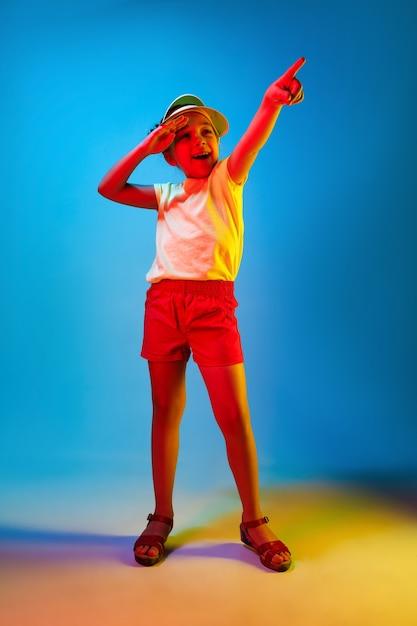 Happy Teen Girl Debout, Souriant Et Pointant Vers Le Haut Sur Studio Néon Bleu Branché Photo gratuit