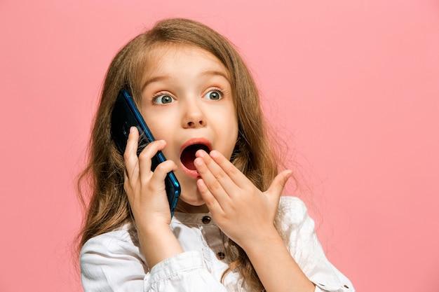 Happy Teen Girl Debout, Souriant Avec Téléphone Mobile Sur Studio Rose à La Mode Photo gratuit