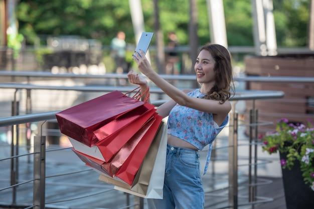 Happy time to shopping concept, femme asiatique tenant des sacs à provisions et selfie elle-même avec le smartphone dans les mains au centre commercial. Photo Premium