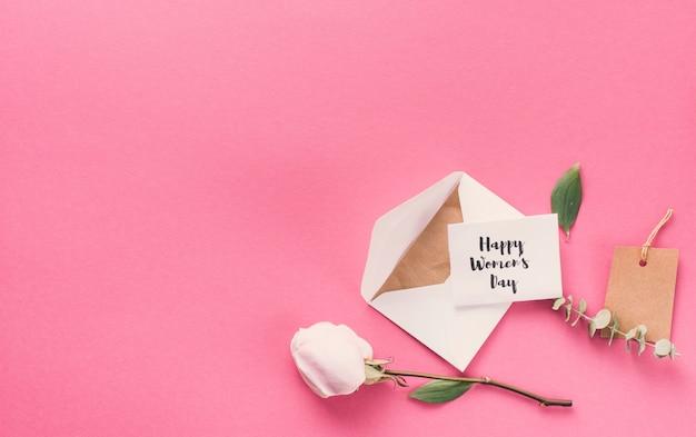 Happy womens day inscription avec enveloppe et fleur sur la table Photo gratuit