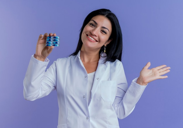 Happy Young Female Doctor Wearing Medical Robe Holding Pack De Capsules Médicales à La Recherche Et Montrant La Main Vide Photo gratuit
