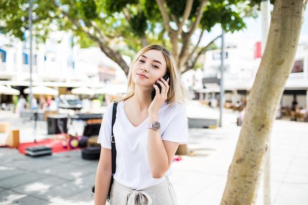 Happy Young Woman Talking On Phone At City Street Lifestyle Portrait En été Photo gratuit