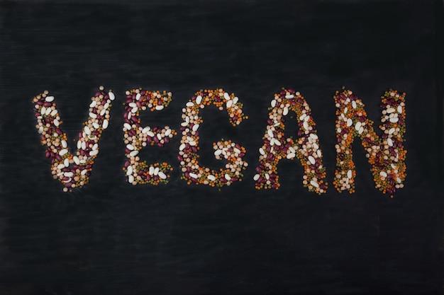 Haricots, lentilles, haricot mungo, petits pois disposés sur un fond en bois noir sous la forme de l'inscription vegan Photo Premium
