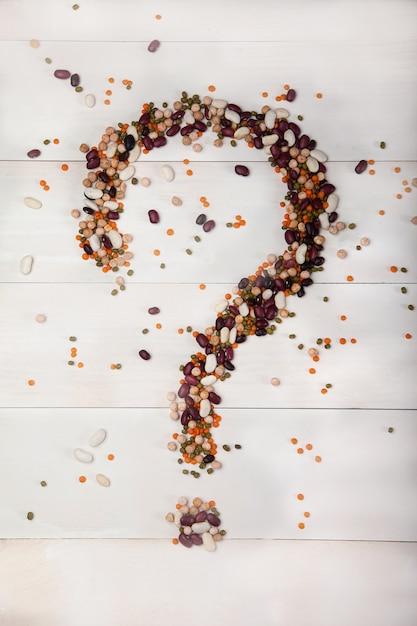 Haricots, lentilles, pois disposés sur un fond en bois blanc sous la forme d'un point d'interrogation Photo Premium