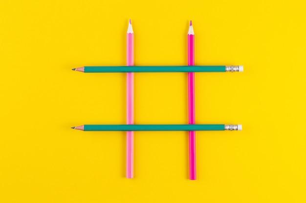 Hashtag Signe De Crayons Colorés Croisés Sur Une Surface Jaune Photo Premium