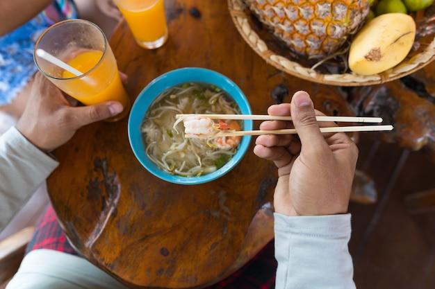 Haut, angle, vue, homme, manger, nouilles, baguette, et, boire, jus orange, essayer, traditionnel, as Photo Premium