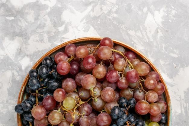 Haut De La Page Vue Rapprochée De Différents Raisins Juteux Fruits Aigres Moelleux Sur Un Bureau Blanc Léger Fruits Frais De Jus De Vin Photo gratuit