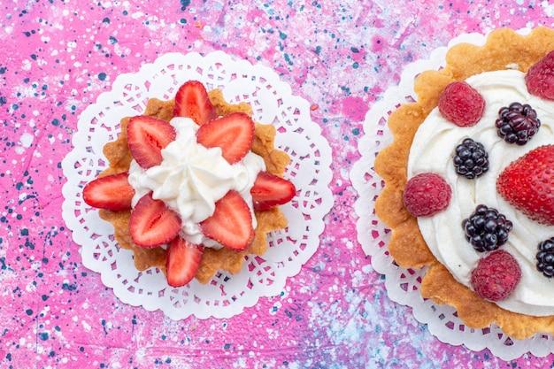 Haut De La Page Vue Rapprochée De Petits Gâteaux Crémeux Avec Différentes Baies Sur Blanc Clair Photo gratuit