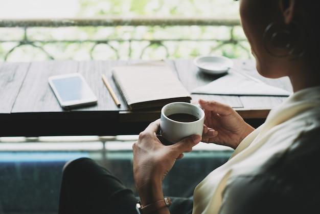 Haut plan d'une femme méconnaissable assise sur un balcon et tenant une tasse de café Photo gratuit