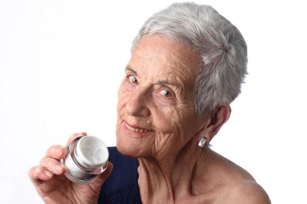 Haute femme appliquant une crème pour la peau ou un hydratant sur son visage Photo Premium