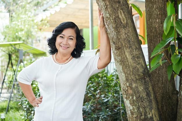 Haute femme asiatique qui pose dans le jardin et s'appuyant sur un arbre Photo gratuit