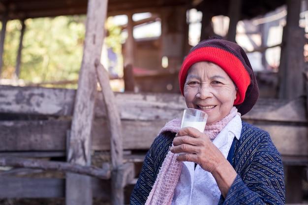Haute Femme Asiatique Tenant Un Verre De Lait à La Maison Dans La Campagne De La Thaïlande. Photo Premium