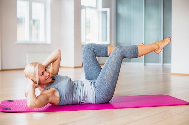 Haute femme faisant des abdos sur un tapis de yoga Photo gratuit