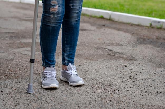 Haute femme en jeans marche avec canne à l'extérieur. Photo Premium
