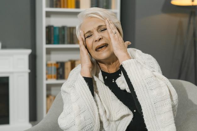 Haute Femme Soupire émotionnellement En Touchant Ses Tempes Avec Ses Mains Photo Premium
