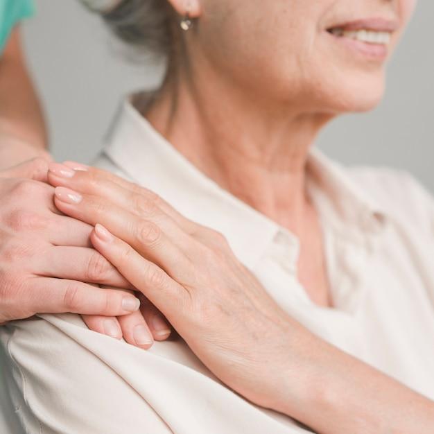 Haute femme touchant la main de l'infirmière Photo gratuit