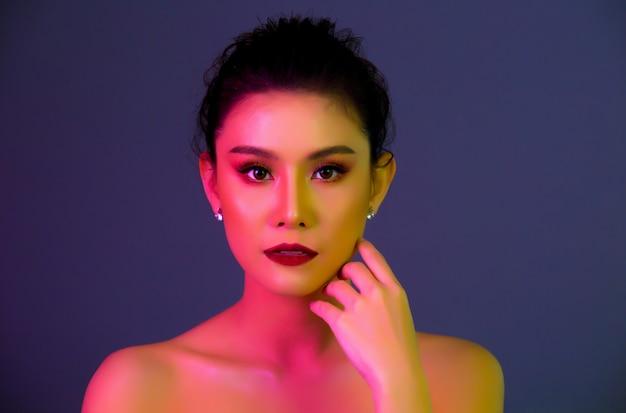 Haute modèle femme dans des lumières colorées posant Photo gratuit