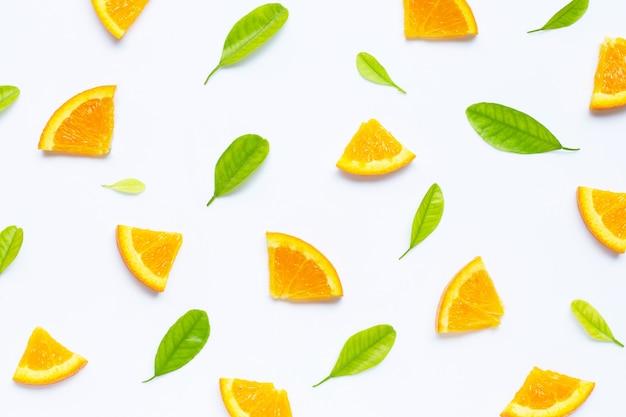 Haute teneur en vitamine c, juteuse et sucrée. fruits orange frais avec motif sans soudure de feuilles vertes Photo Premium