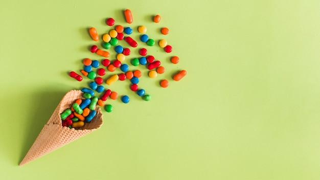 Haute vue angle, de, bonbons, répandre, depuis, cornet glace crème, sur, fond vert Photo gratuit