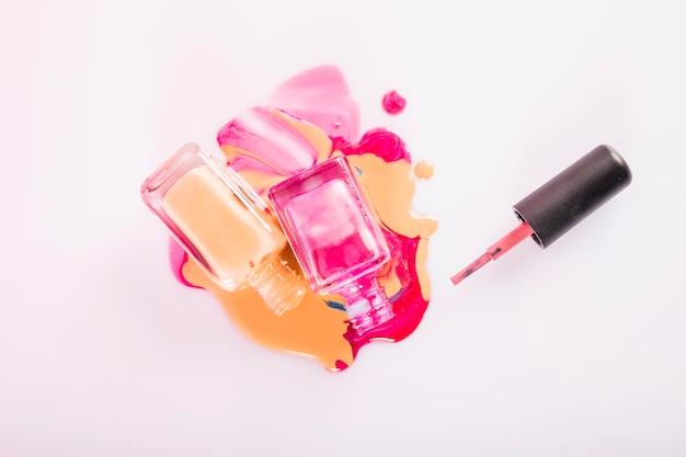 Haute vue angle, de, bouteilles renversé, vernis à ongles, sur, rose, toile de fond Photo gratuit