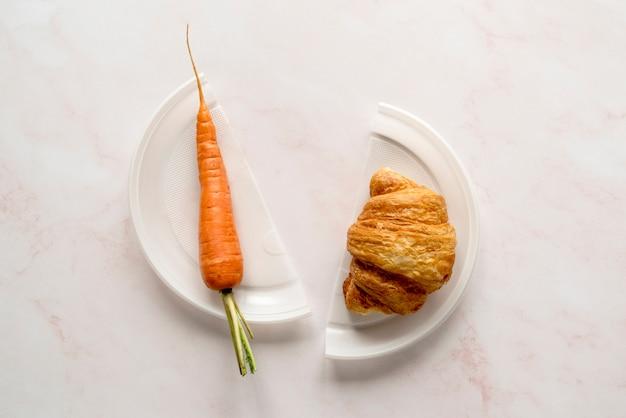 Haute vue angle, de, carotte, et, croissant, sur, plaque cassée Photo gratuit