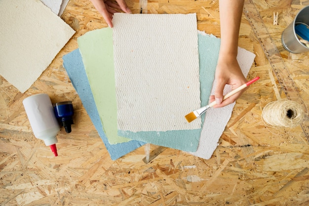 Haute vue angle, de, a, femme, main, utilisation, pinceau, sur, fait main, papiers Photo gratuit