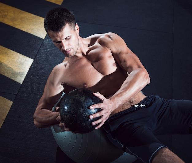 Haute vue angle, de, forme, jeune homme, exercice, à, médecine-ball Photo gratuit