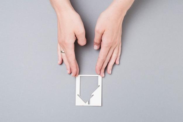 Haute vue angle, de, main féminine, toucher, découpage maison, sur, fond gris Photo gratuit