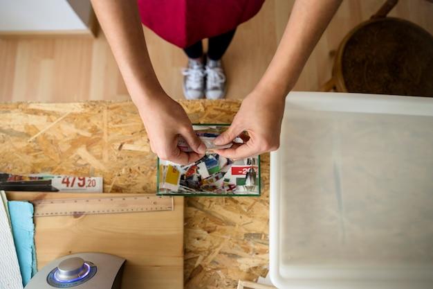 Haute vue angle, de, main femme, déchirer, papier, dans, morceaux, dans, atelier Photo gratuit
