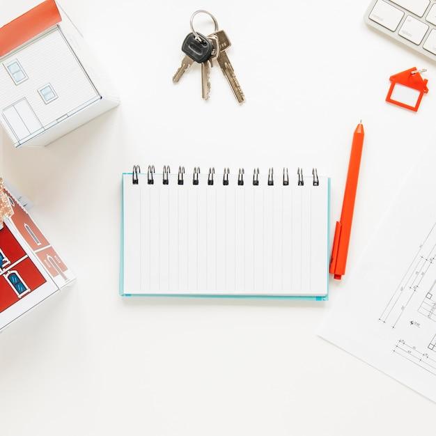 Haute vue angle, de, modèle maison, près, spirale, bloc-notes, clés, stylo, fond blanc Photo gratuit