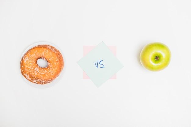 Haute vue angle, de, pomme verte, contre, beignet, sur, fond blanc Photo gratuit