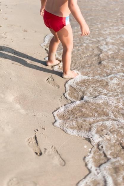 Haute Vue Enfant Jouant Au Bord De La Mer Photo gratuit