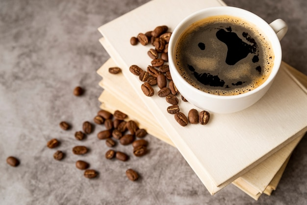 Haute vue tasse de café sur des livres Photo gratuit