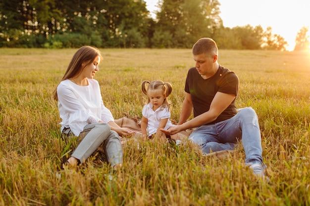 Héhé Dans Un Champ En Automne. Mère, Père Et Bébé Jouent Dans La Nature Dans Les Rayons Du Coucher Du Soleil Photo gratuit