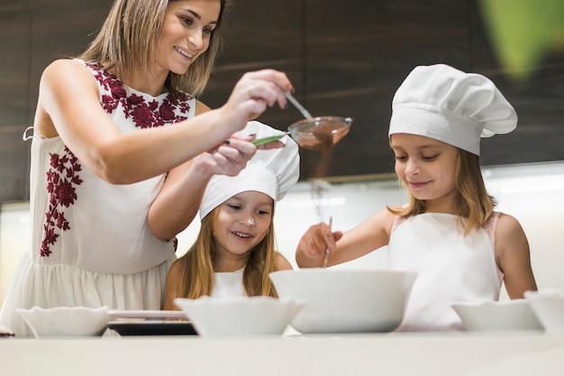 Héhé, préparer un repas pendant que la mère filtre la poudre de cacao à travers une passoire dans la cuisine Photo gratuit