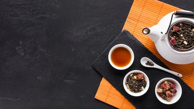 Herbe de thé séchée et fleur d'orchidée rose et fond texturé noir Photo gratuit