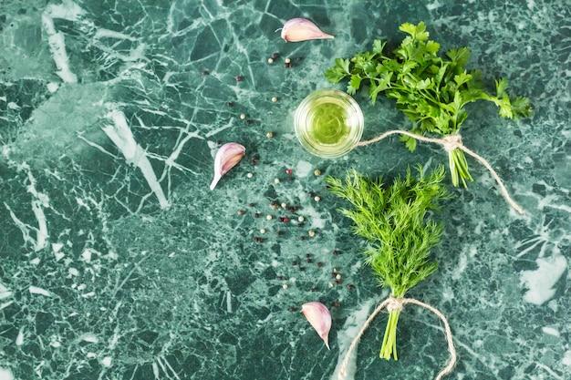 Herbes et épices sur la vue de dessus de table en pierre marbre. persil, aneth, ail, huile d'olive et poivre Photo Premium