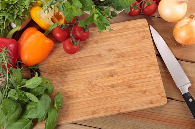 Les Herbes Et Les Légumes Avec Une Planche à Découper Photo gratuit