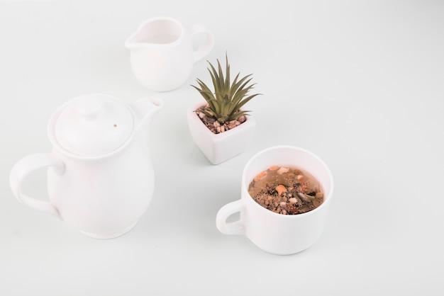 Herbes séchées dans le thé près de la vaisselle sur fond blanc Photo gratuit