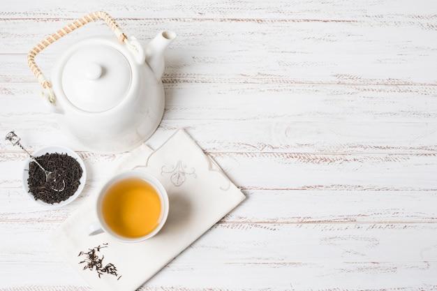 Herbes et tasse de thé avec théière sur un bureau en bois texturé blanc Photo gratuit